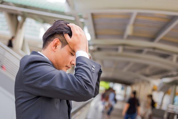 ビジネスの男性は彼の仕事の後に疲れているか、ストレスを感じています。重点を置かれた実業家概念のイメージ。