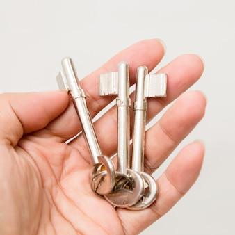 Рука держа ключ изолированный на белизне. студийное освещение.