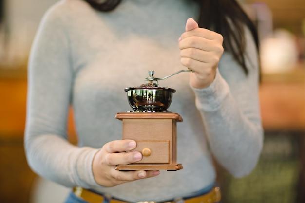 ビンテージコーヒーグラインダーでコーヒーを手で挽くバリスタ