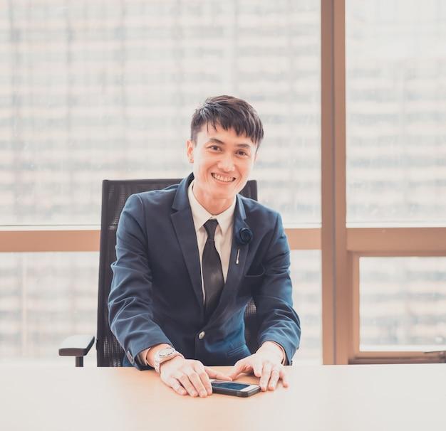 近代的なオフィスの若いアジア系のビジネスマンの肖像画。ビジネスのコンセプト