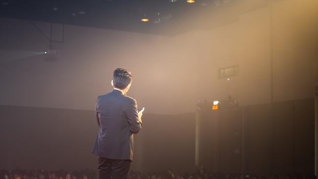 Спикер на сцене и разговор о бизнесе в комнате для семинаров