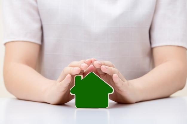 女性の手の下の家。保険および家の保護の概念。