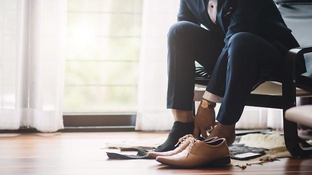 ビジネスマンや新郎は彼の靴に靴ひもを結んだ。