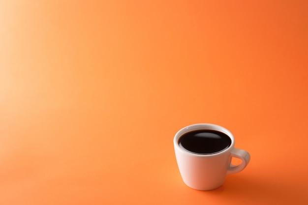 オレンジ色の背景のコーヒーカップ