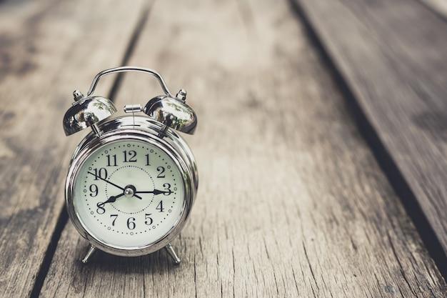 古い木製の食卓にレトロな目覚まし時計