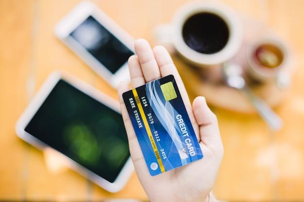 Молодая женщина расплачивается за кафе с помощью кредитной карты