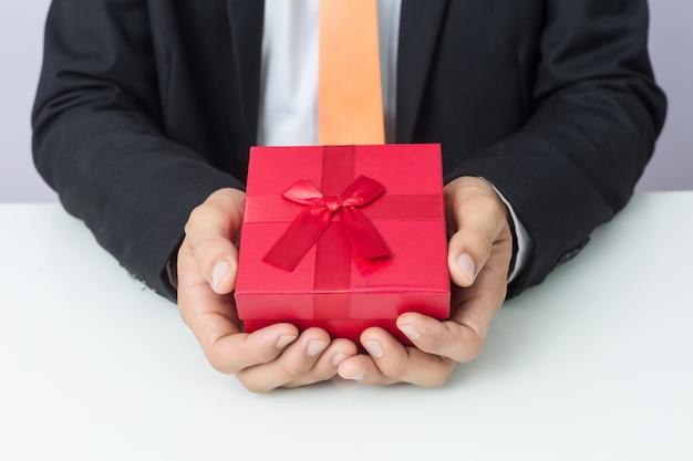 ビジネスマンは、ギフト用の赤いボックス、孤立した背景を保持します