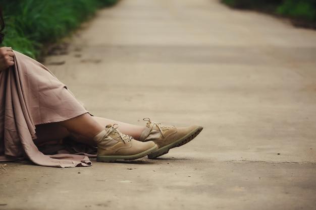 地元の道路に座っているブーツを持つ女性