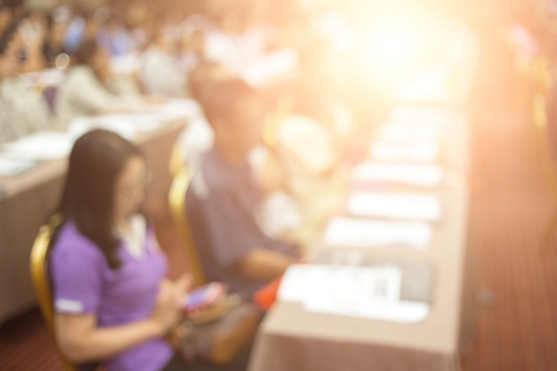 クラウンは、ビジネス会議で講演するスピーカーを聞いています。会議ホールの聴衆。ビジネスと起業家精神。