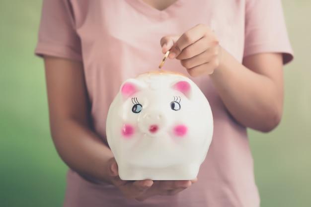 貯金箱、貯金箱にコインを入れる少女