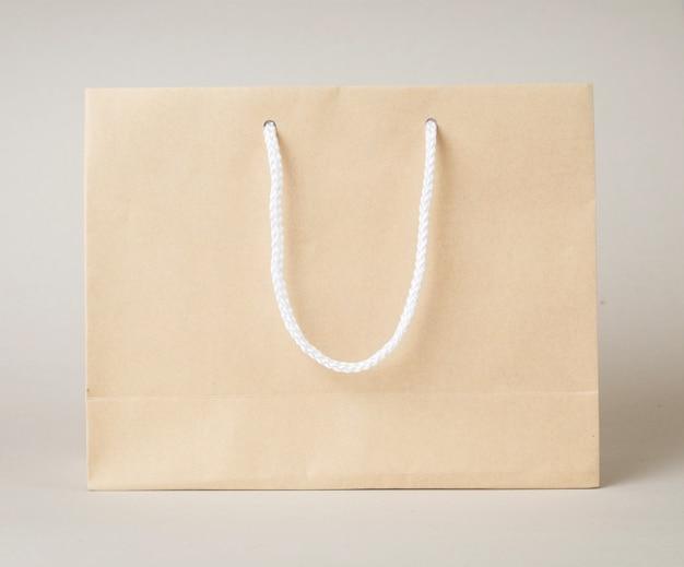 Коричневая сумка для покупок на белом фоне и место для текста или продукта