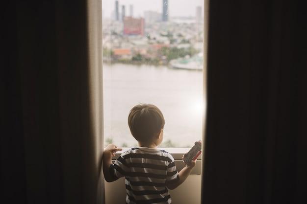 ウィンドウを開くアジアの若い男の子
