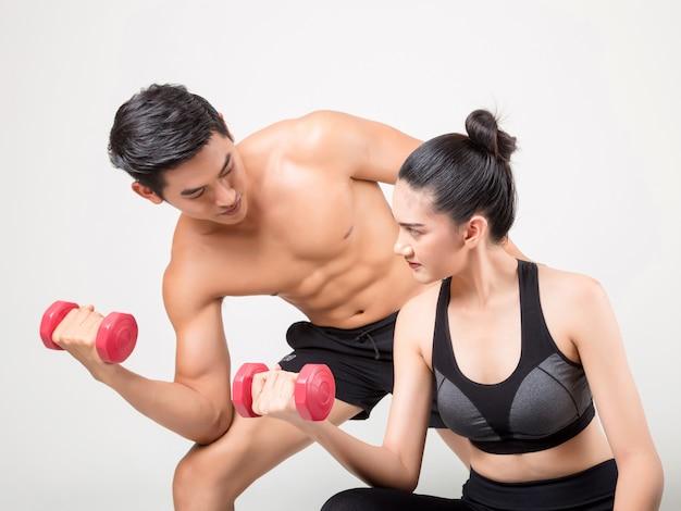 幸せな若いフィットネス男とトレーニング時間で彼のガールフレンド。フィットネスと健康的なライフスタイルのコンセプト。白い背景で撮影スタジオ。