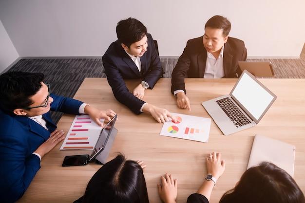 会議室でのビジネス人分析コストグラフとのチームワーク