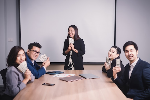 ビジネスチームの成果と会議中に上司からドル紙幣を取得