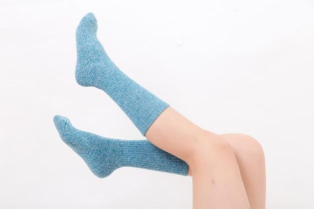 彼の足で青い靴下を着ている若い女性の素足のクローズアップ。白い背景に分離します。スタジオ照明