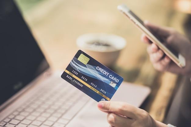 プラスチック製のクレジットカードを保持しているとラップトップを使用して容女性の手。オンラインショッピングまたは支払いの概念。