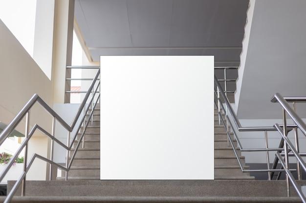 Пустой рекламный щит, расположенный в подземном зале, рядом со ступеньками