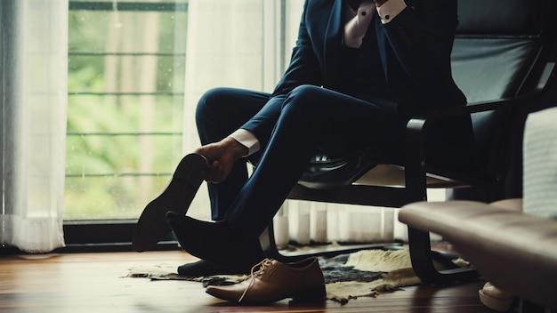 Бизнесмен или жених связали шнурок на его обуви.