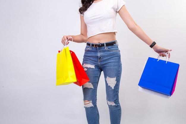 Молодые женщины с покупками на белом