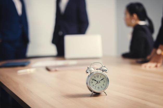 セミナールームのビジネス人々とテーブルの上の目覚まし時計。チームワークをブレインストーミングする企業の成功に応える
