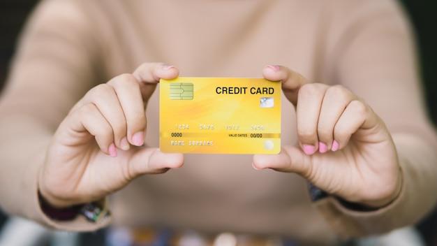 Молодая женщина держа кредитную карточку, онлайн покупки или оплачивая концепцию.