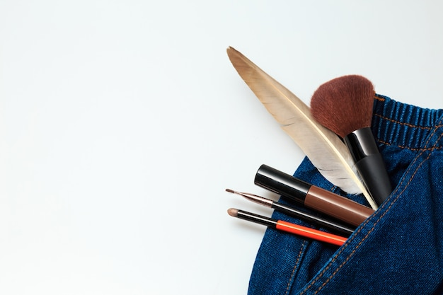 女性のデニムジーンズからこぼれる化粧品と化粧品の美容製品