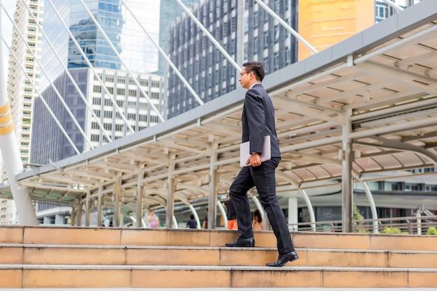 ビジネスの男性とラッシュアワーで階段を上って行く彼のラップトップを持つ