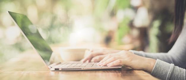 Молодая женщина, сидя в кафе на деревянный стол, пить кофе и с помощью ноутбука.