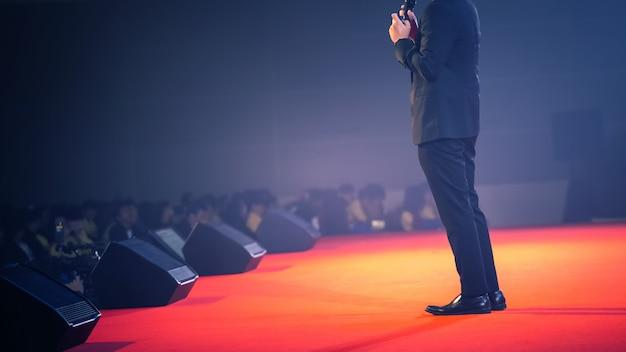 ステージ上のスピーカーとセミナールームでのビジネスについて話す