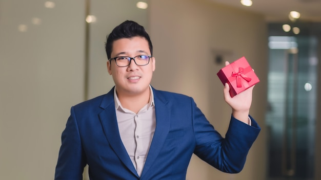 Бизнесмен держит красную подарочную коробку