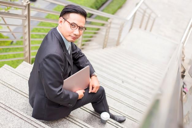 ビジネスの男性は、近代的な都市で彼のラップトップ屋外で働いています。