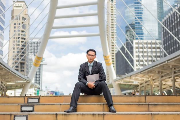 彼のラップトップコンピューターを屋外でスーツの若いアジア実業家