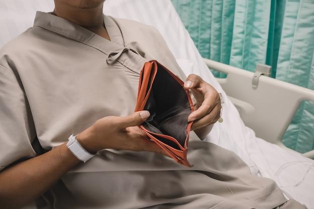 Пациент показывает пустой кошелек в больнице