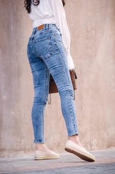 Счастливая азиатская женщина в ярко-синих джинсах скинни