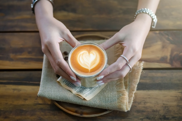 コーヒーカップ、上にハートラテアートとラテ