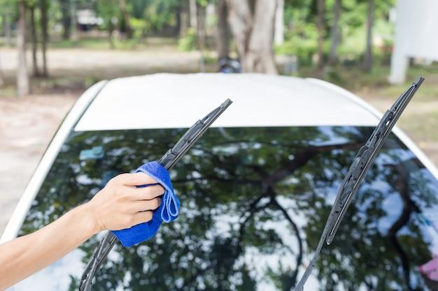 マイクロファイバーの布で車を掃除する男-車の詳細と従順な概念