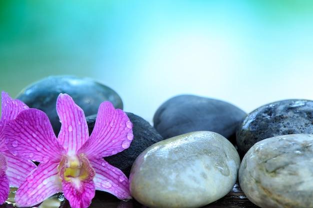 テキストまたは製品のコピースペースを持つ木製のテーブルに禅石とピンクの蘭