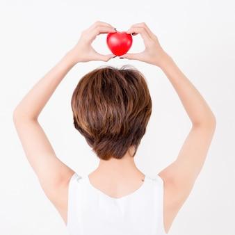 彼女の頭に赤いハートを持つ美しい若いアジア女性の裏側。心血管の健康のためのコンセプト。