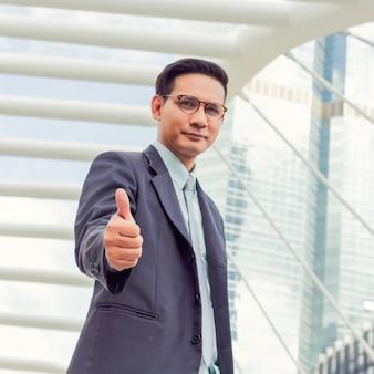 ビジネスおよびオフィスのコンセプト。親指を現して若いアジアのハンサムな実業家。