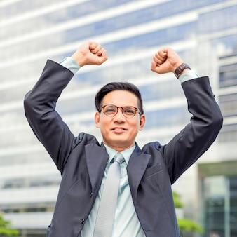 Празднование успеха. счастливый бизнесмен стоя на улице зданий