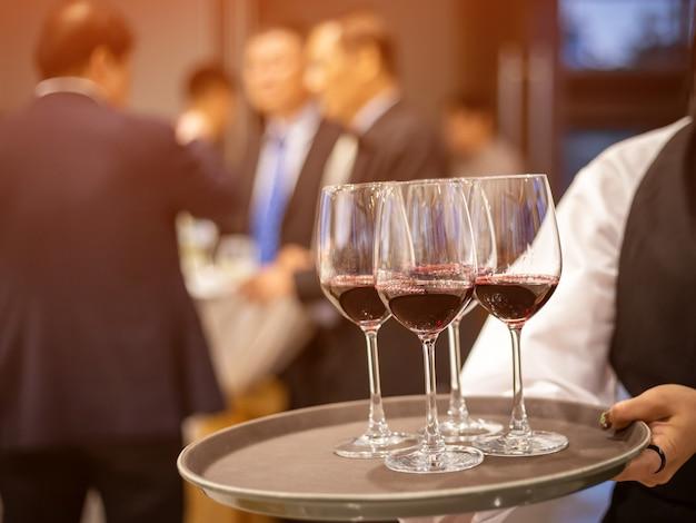 Официант подает бокалы с красным вином
