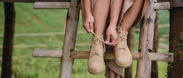 階段の上に座って、ブーツを着ている女性