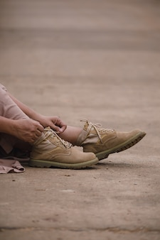 地元の道路の上に座ってブーツを持つ女性