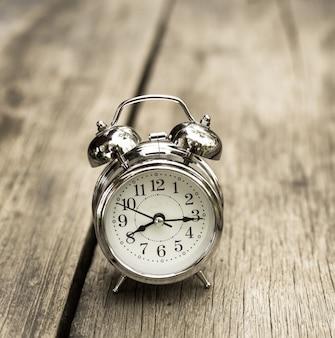 古い木製のテーブルにレトロな目覚まし時計