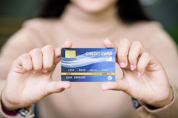 プラスチック製のクレジットカードを持っている龍女性手
