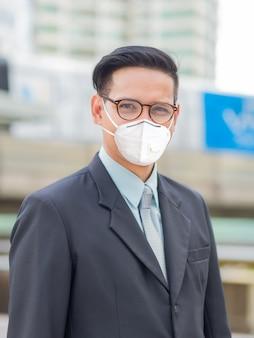 街でマスクを持った若いビジネスマン