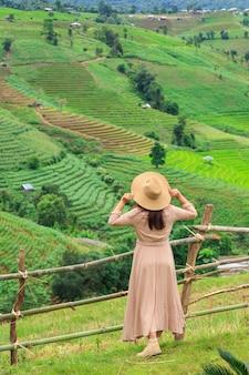 帽子を持つ女性と山、パボンペアン、メージャム、チェンマイ、タイを見て