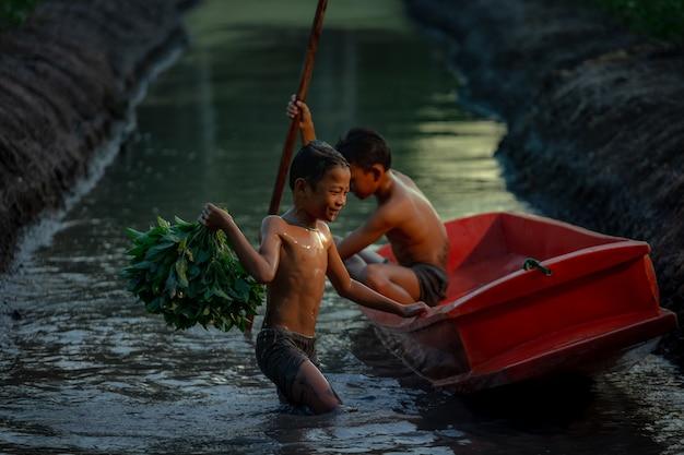 ラーチャブリー県のダムヌンサドアック水上マーケット近くの野菜農場で遊んでいる少年