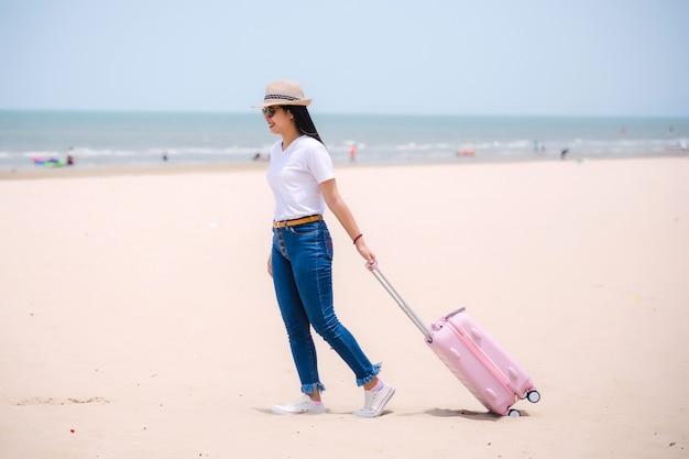 旅行の人々の概念。ビーチで若い幸せなアジアグリル